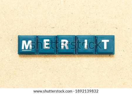 Tile alphabet letter in word merit on wood background Stockfoto ©