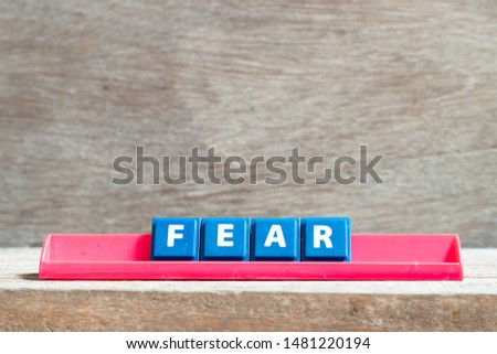 Tile letter on red rack in word fear on wood background #1481220194