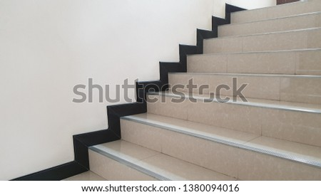 Tile stairs with stainless steel stair nosing and black skirting board.