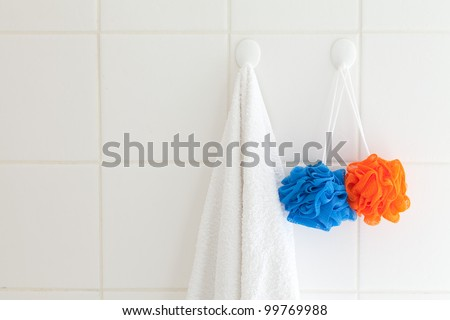 Tiled bathroom wall with towel on one hook and facecloth on another. - stock photo