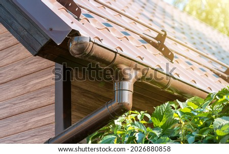 Tiled roof with segment of snow holding structure, Gutter system for metal roof. Holder gutter drainage system Photo stock ©