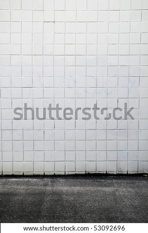 Tiled wall with a blank white bricks and gray spray painted graffiti.