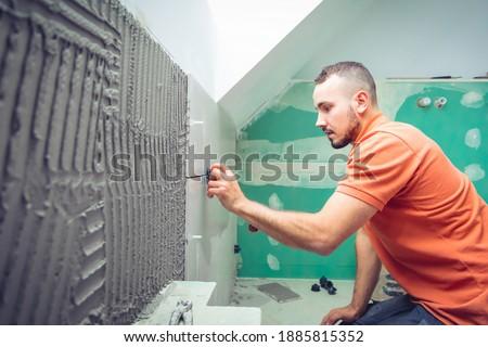 tiler installing large format tiles during home renovation  Foto stock ©