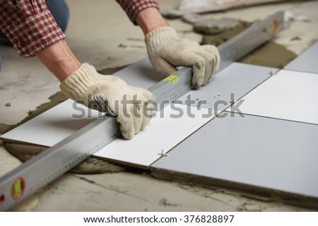 Tiler installs ceramic tiles on a floor