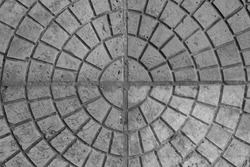Tiles laid out in a circle, cross in the center, black and white monochromatic background.