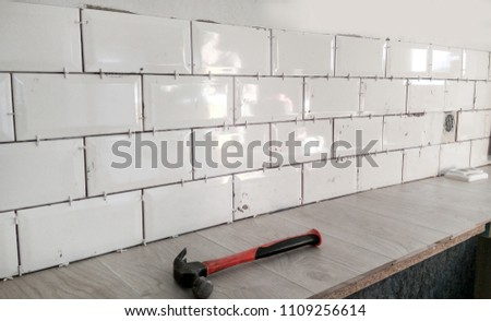 Tiling the tiles in the kitchen. Ceramic brick tile wall in process #1109256614