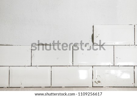Tiling the tiles in the kitchen. Ceramic brick tile wall in process #1109256617