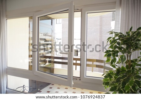 Tilt-and-turn white pvc window in living room, opened