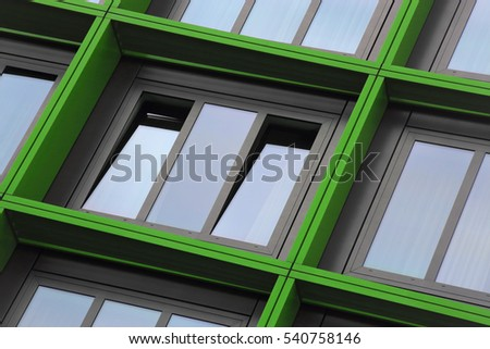 Tilt close-up photo of ajar windows in green frames. Eco-friendly technologies / energy saving motif. Building exterior detail. Abstract photo on the subject of modern architecture. #540758146