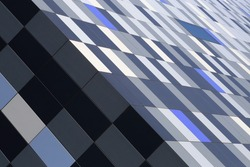 Tilt close-up photo of office building corner covered with multicolor tiles. Abstract modern architecture background with distinctive checkered pattern.