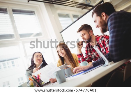 Tilt image of photo editors discussing about document in meeting room at office #574778401