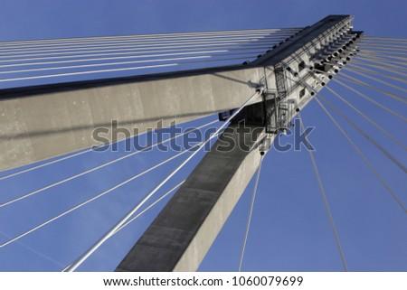 Tilt photo of cable-stayed bridge / suspension bridge against the background of blue sky. Modern urban architecture. Hi-tech cityscape fragment. #1060079699