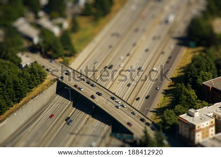 Tilt shift detail of bridge crossing interstate highway with cars in the middle of city - stock photo