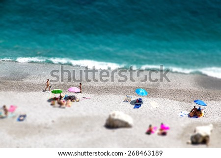 Tilt shift of Ocean beach view with beautiful waves of clean transparent water and white sand, high altitude view of beautiful seashore with sunbathe people, vacation and holiday concept, blur effect - stock photo