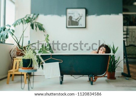 Tilt shift portrait of young beautiful girl in pink dress lying in empty vintage cast-iron bath inside decorative in french style room with green plants. Odd unusual strange woman home relaxation #1120834586