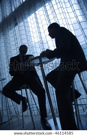 Tilt view silhouette of African-American and Asian businessmen sitting at a table and having coffee in front of a curtained window. Vertical format.