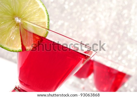 Tilted composition of cosmopolitan cocktails with lime slice against a sparkle background.   Macro with shallow dof and copy space.