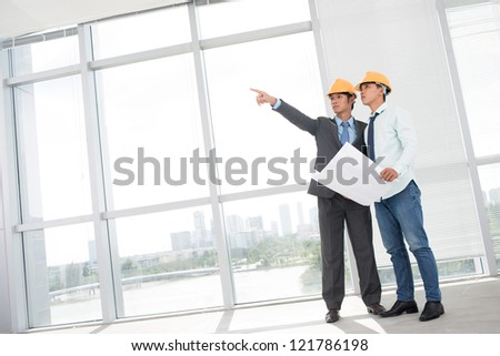 Tilted image of two supervisors comparing blueprint with actual building interior