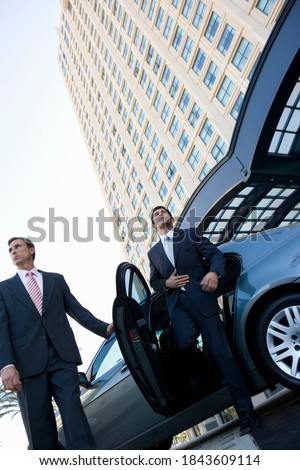 Tilted low angle shot of a businessman exiting a car with the door held open by the chauffeur in front of a skyscraper.