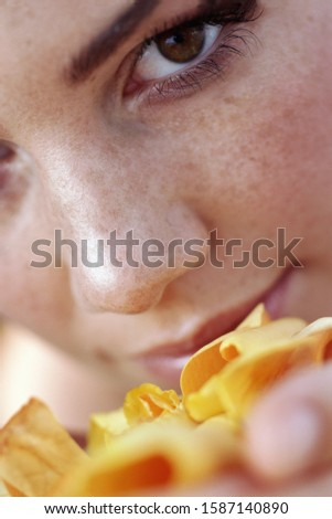 Tilted portrait of a young woman holding flower petals