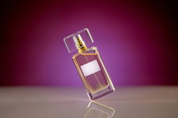 Tilted unbranded perfume bottle on glassy surface, magenta gradient background. Beauty and fashion concept