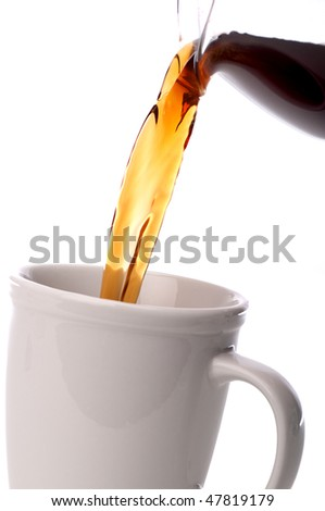 tilted vertical close up coffee being poured into a coffee cup