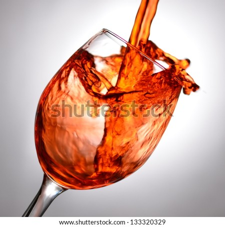 Tilted wine glass filled up with red liquid until splash with grey or off-white background