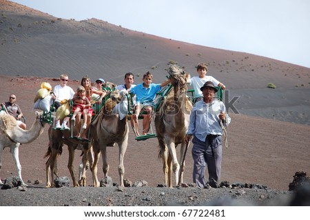 TIMANFAYA NATIONAL PARK, LANZAROTE, SPAIN - JUNE 10: Tourists ride on camels being guided by local people through the famous Timanfaya National Park in June 10, 2009