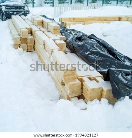 Timber balks partly covered with plastic cover and abandoned outdoor due to blizzard Stockfoto ©