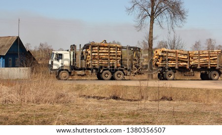 Timber carrier transports logs on a trailer on rural road on a spring day against a field and country house - commercial timber cutting, wood trading #1380356507