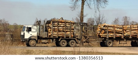 Timber carrying vehicle transports logs on a trailer on a country road on a spring day - commercial timber, wood trading #1380356513