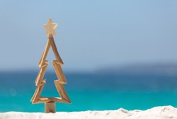 Timber Christmas tree with star sits in pristine white sand with idyllic beach background.  A summer Christmas.