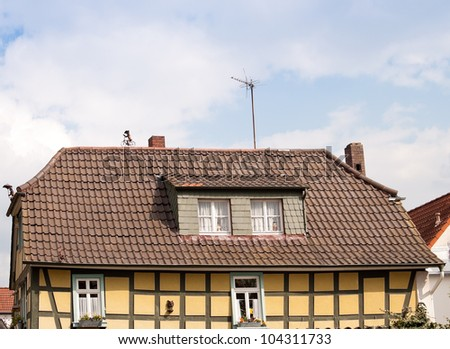 Timber framed house with two figurines on roof