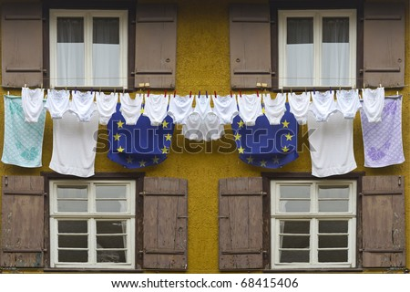 Timber framing house with europe flag colored laundry hanging on a clothesline