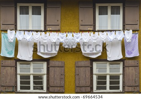 Timber framing house with several pieces of laundry hanging on a clothesline