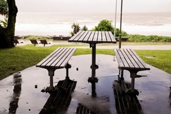 Timber table and stools for outdoor beachfront dining with an ocean view on a wet and rainy day