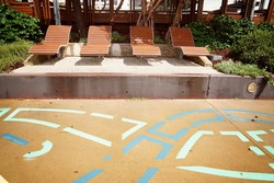 Timber tourist loungers beside a colorfully painted footpath on the beachfront