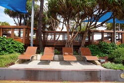 Timber tourist loungers beside a water park on the beachfront