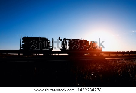 Timber truck transports timber logs and timber against the backdrop of a sunset and a blue sky, logistics and freight concept, copy space