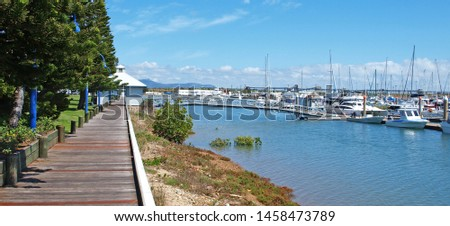 Timber waterfront boardwalk at picturesque Keppel Bay Marina with tropical water, boats, shrubs, and blue sky background. Safe haven for sailing and cruising vessels. The Great Barrier Reef, #1458473789