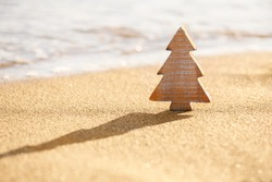 Timber wooden Christmas tree on a sand on the tropical beach near ocean, summer Christmas and winter holyday concept, selective focus. Happy New Year background. Zero waste Christmas