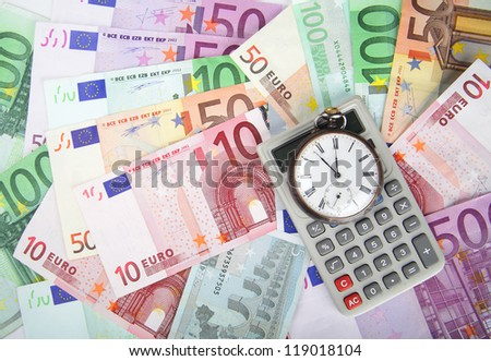 Time and Money concept image.  Close-up of euros and vintage watch and calculator.