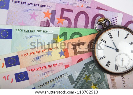Time and Money concept image.  Close-up of  Euros  with vintage watch.