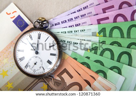 Time and Money concept image. Euro banknotes with vintage watch.