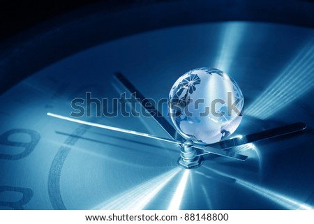 Time concept. Closeup of glass globe lying on blue metal clock face