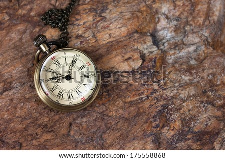 Time concept, old watch on a textured rock.