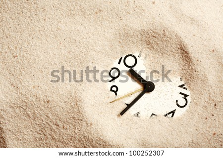 Time concept. Sand background with clock face