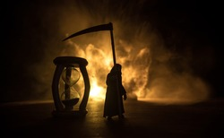 Time concept. Scary view of grim reaper silhouette standing at hourglass with smoke and lights on a dark background. Surreal decorated picture