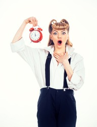 Time concept. Time management. Surprised woman holds an alarm clock in her hand. Red clock with alarm on girl hand on a white background. Age, aging.