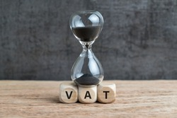 Time countdown for VAT increase deadline concept, hourglass or sandglass on cube wooden block with alphabets VAT, Value Added Tax on wood table with dark black loft cement wall.